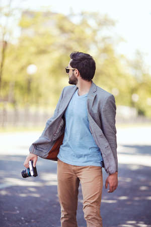 Male photographer camera walking outside on the city street . Portrait of handsome man in casual clothes outdoors