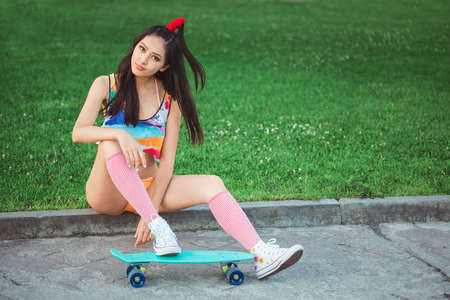 Attractive sporty asian woman in swimsuite smiling and sitting with skateboard in city park. Sport and summer holiday concept portrait. Gorgeous playful model posing with board. Young happy girl in bikini looking at camera.