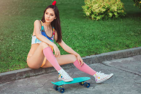 Attractive sporty asian woman in swimsuite and sitting with skateboard in city park. Sport and summer holiday concept portrait. Gorgeous fashion model posing with board. Young happy girl in bikini looking away.