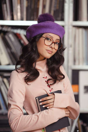 Vrouw die in de bibliotheek bestudeert. Portret van het aantrekkelijke zekere Aziatische boek van de meisjesholding binnen tegen boekenrek. Elegante dame die trendy kleding en leuke hoed draagt en camera bekijkt. Schoonheid mode shot van prachtige slanke model.