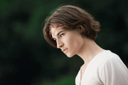 Portret przystojny mężczyzna z koroną w lesie. Książę elfów. Szlachetny elf wróżka w magicznym lesie. Fantazja. Bajka. Zdjęcie Seryjne