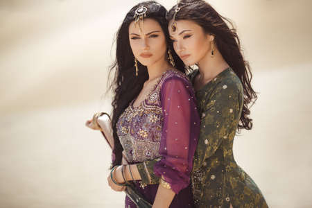 Travel concept. Adventure of two sisters serious princesses standing in the desert and looking at landscape. Two beautiful mixed race asian caucasianl girls enjoy a joint journey. Creative art fashion portrait shot of two gorgeous attractive models with luxury make-up and hairstyle outdoors in arabian indian dresses. Copy space background on sand dunes. Standard-Bild