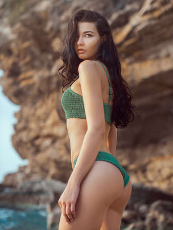 Portrait of beautiful woman on the sea. Close-up portrait of beautiful sensual brunette mixed race Asian Caucasian woman standing on the beach.