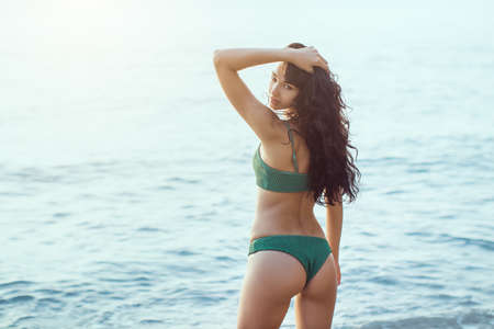 Romantic young girl in bikini outdoors against ocean background. Portrait of beautiful sensual brunette mixed race Asian Caucasian woman standing on the beach. Slim female model resting on the sea shore and looking at camera. The wind fluttering hair. Back view.