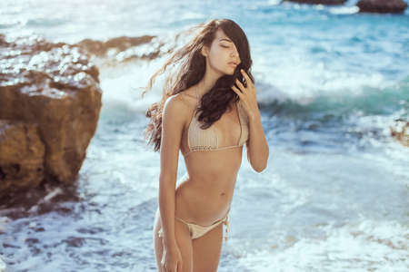 Romantic young girl in bikini outdoors against ocean background. Portrait of beautiful sensual brunette mixed race Asian Caucasian woman standing on the beach. Slim female model resting on the sea shore and looking at camera. The wind fluttering hair.