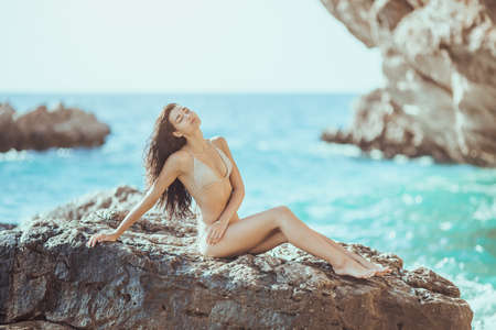 Romantic passion young girl in bikini outdoors against wild tropical sea background. Beautiful sensual brunette mixed race Asian Caucasian woman with slim sporty tanned body sitting on rock in water. Attractive perfect female model resting on rocky sea shore with closed eyes. The wind fluttering hair Stock Photo