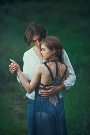 Young couple of elves in love standing in magical forest outdoor on nature. Fairy tale love, relationship and magik people concept. Man holding woman by hands and ambracing