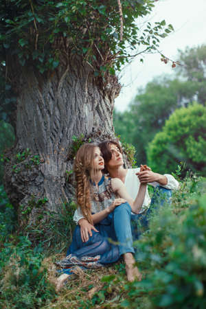 Young couple of elves in love sitting in magical forest agaist the big tree outdoor on nature. Fairy tale of love, relationship and magik people concept. Man ambracing woman Stock Photo