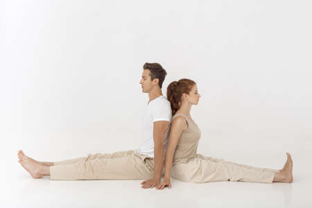 Young couple practicing yoga, sitting back to back indoors on white abstract polygon background. Young caucasian woman and man smiling and meditating together in acroyoga pose in tantra school. Full length shot. Yoga practice group concept. Calmness and relax, family happiness.