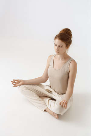 Young girl practice yoga on white background. Portrait of gorgeous caucasian red hair woman doing yoga or pilates exercise indoor, sitting in lotus pose, namaste. Full length shot. Calmness and relax, female happiness. Stock Photo