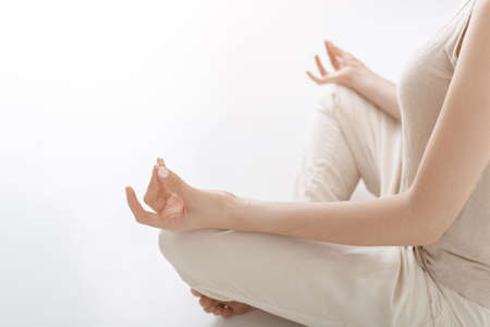 Close up hands. Woman do yoga indoor. Woman exercising vital and meditation for fitness lifestyle club against white background. Concept Yoga