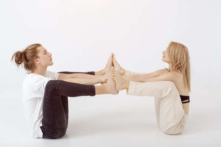 Young athletic couple practicing acroyoga. Balancing in pair indoors on white background. Young caucasian blonde woman and man sitting and meditating with closed eyes together in yoga pose in tantra school. Full length shot. Yoga practice group concept. Calmness and relax, family therapy.