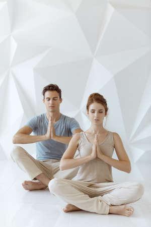 Jong koppel beoefenen van yoga binnenshuis op witte abstracte veelhoek achtergrond. Jonge vrouw en man zitten en mediteren met gesloten ogen samen in lotus houding in tantra school. Volledig schot. Yoga praktijk groep concept. Kalmte en ontspanning, gezinsgeluk. Stockfoto