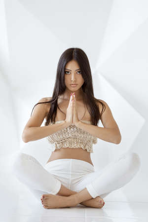 Asian girl practice yoga on white abstract polygon background. Portrait of gorgeous young woman doing yoga or pilates exercise indoor, sitting in lotus pose, namaste. Full length shot. Calmness and relax, female happiness.