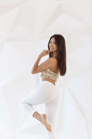 Attractive fitness asian woman indoors on white abstract polygon background. Casual mixed-race Asian Caucasian girl smiling looking happy in light casual sporty sexy clothes. Gorgeous sexy model posing in studio and looking at camera Stock Photo