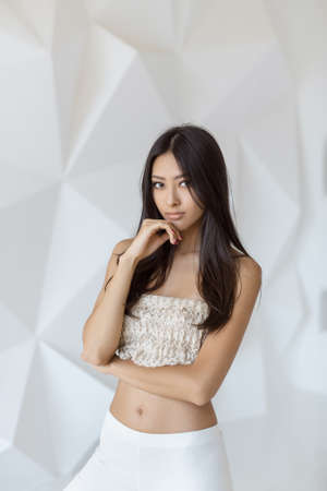 Asian woman thinking indoors on white abstract polygon background. Stock Photo