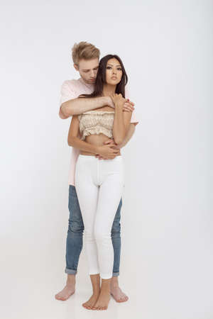 Romantic young mixed-race couple indoors in studio against white background. Interracial couple, Caucasian man holding with love his asian girlfriend from behind, posing at camera in full length. People in love, relationship, dating, lovers, romantic concept. Stock Photo