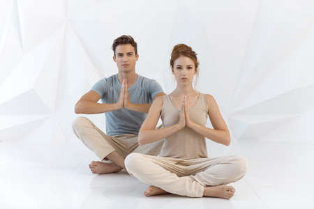Young couple practicing yoga indoors on white abstract polygon background. Young woman and man sitting and meditating together in lotus pose in tantra school. Full length shot. Yoga practice group concept. Calmness and relax, family happiness.