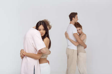 Two young couples in love hug each other indoors. Stock Photo