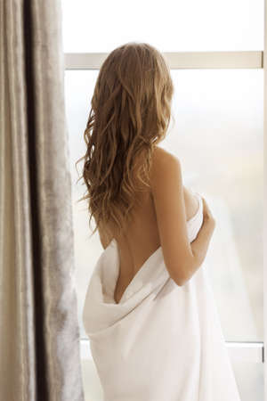 Gorgeous naked blonde woman covering her body with a blanket and looking sensually through window in the morning. Art boudoir fashion photo of beautiful sexy girl with big breast indoors at home. Slim model Perfect body. Beauty and health. Rear view