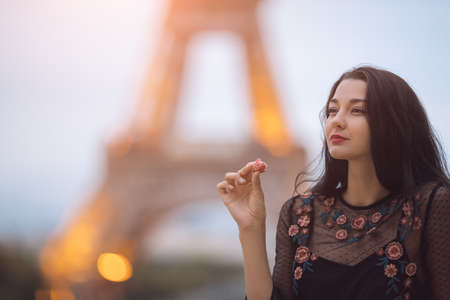 Paris woman smiling eating the french pastry macaron in Paris.