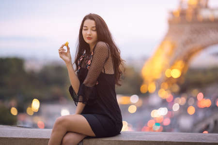Paris woman smiling eating the french pastry macaron in Paris. Evening Eiffel tower with lights in the background. Gorgeous romantic young sensual girl in fashion black sexy dress enjoying traveling outdoors during holidays in Europe. Cute beautiful mixed race Asian Caucasian female model sitting at Trocadero view point. Standard-Bild