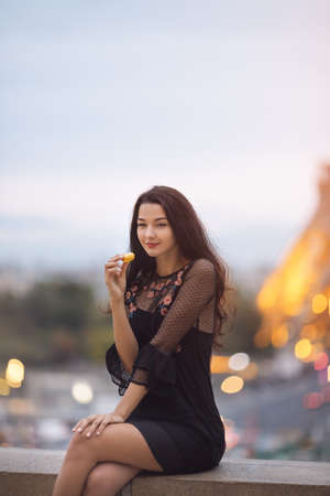 Paris woman smiling eating the french pastry macaron in Paris. Evening Eiffel tower with lights in the background. Gorgeous romantic young sensual girl in fashion black sexy dress enjoying traveling outdoors during holidays in Europe. Cute beautiful mixed race Asian Caucasian female model sitting outdoors. Standard-Bild