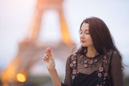Paris woman smiling eating the french pastry macaron in Paris. Evening Eiffel tower with lights in the background. Portrait of gorgeous romantic young sensual girl in fashion black sexy dress enjoying traveling outdoors during holidays in Europe. Cute beautiful mixed race Asian Caucasian female model sitting outdoors Stock Photo
