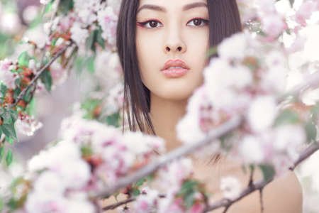 Perfect model with creative vivid makeup and pink lipstick on lips and traditional japanese hairstyle posing outside.