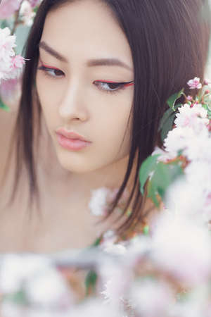 Outdoor fashion photo of beautiful young asian woman surrounded by flowers on spring. Stock Photo