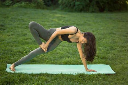 Woman practicing yoga performing yoga-asanas. Young attractive slim girl in bodysuit relaxing and doing exercises Stock Photo