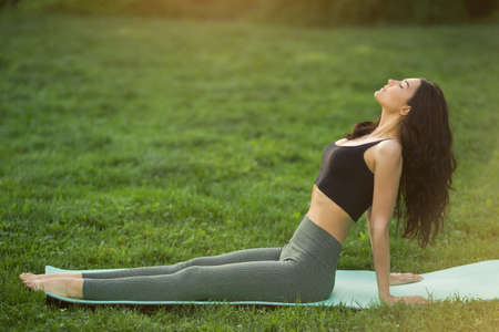 Healthy sports lifestyle. Young woman doing workout for stretching body. Young attractive slim girl in bodysuit doing exercises. Stock Photo