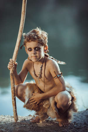 Cute caveman, manly boy with staff hunting. Prehistoric tribal boy outdoors on nature. Young shaggy and dirty savage, warrior and hunter. Primitive ice age man in animal skin sitting against river. Actor playing role in movie. Reconstruction of Neanderthal and cro-magnon life