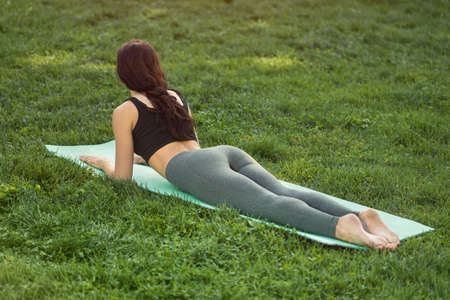 Woman practicing yoga performing yoga-asanas outdoors. Young attractive slim fitness girl in bodysuit relaxing and doing exercises, laying and stretching on a yoga mat. Gorgeous mixed race Asian Caucasian young model training outside on nature during holidays. Side back view Stock Photo