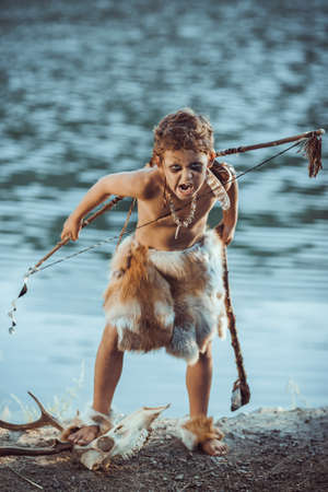 Angry caveman, manly boy with stone axe and bow hunting near river. Prehistoric tribal boy outdoors on nature. Young shaggy and dirty savage, warrior and hunter with weapon. Primitive ice age man in animal skin standing on skull of wild animal and screaming. Actor playing role in movie. Heroic look. Reconstruction of Neanderthal and cro-magnon life