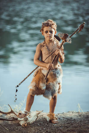 Angry caveman, manly boy with stone axe and bow hunting near river. Prehistoric tribal boy outdoors on nature. Young shaggy and dirty savage, warrior and hunter with weapon. Primitive ice age man in animal skin standing on skull of wild animal Actor playing role in movie. Heroic look. Reconstruction of Neanderthal and cro-magnon life
