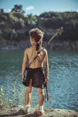 Caveman, manly man with stone axe and bow hunting near river. Prehistoric tribal boy outdoors on nature. Young shaggy and dirty savage, warrior and hunter. Primitive ice age man in animal skin standing against tundra stony landscape. Actor playing role in movie . Reconstruction of Neanderthal and cro-magnon life. Heroic look. Back view Stock Photo