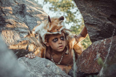 Caveman, manly boy hunting outdoors. Prehistoric tribal boy outdoors on nature. Young shaggy and dirty savage, warrior and hunter hiding in an ambush behind a stone. Primitive ice age man in animal skin portrait. Actor playing role in movie. Reconstruction of Neanderthal and cro-magnon life Stock Photo