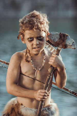 Angry caveman, manly boy with stone axe and bow hunting near river. Prehistoric tribal boy outdoors on nature. Young shaggy and dirty savage, warrior and hunter with weapon. Primitive ice age man in animal skin standing. Actor playing role in movie. Heroic look. Reconstruction of Neanderthal and cro-magnon life