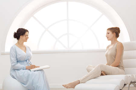 Psychologist having session with her patient in office. Professional psychologist conducting a consultation. Two women communicating indoors. Adult female psychologist working with girl. People in good mood.