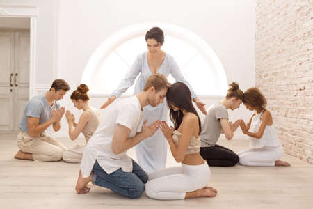 Fitness, yoga and healthy lifestyle concept - group of people doing lotus seal gesture and meditating in seated pose at studio with guru. Group of young multi-ethnic beautiful couples sitting together with closed eyes indoors on tantra courses