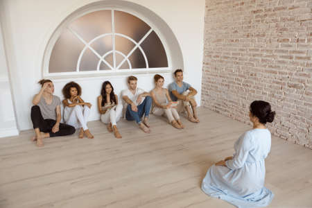 Group therapy session for couples with trust issues. Talk out your problem. Young married couples happy talking while sitting on the therapy session with psychologist. Group of young multi-ethnic beautiful couples sitting together and smiling talking