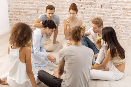 Group of people sitting on floor and eating apples and drinking tea. Young startup businesspeople during lunch break. Group of young multi-ethnic beautiful couples sitting together and smiling talking eating