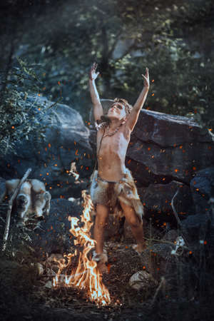Shaman boy at the fire. Scary young primitive boy outdoors near bonfire. Witch craft concept. Angry caveman, manly boy with horns near bonfire. Prehistoric tribal man outdoors on nature making spiritual ritual. Primitive ice age man in animal skin in forest. Creative art fantasy photo