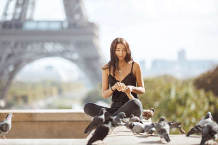 Happy travel woman near the Eiffel tower, Paris. Travel tourist girl on vacation resting happy outdoors. Attractive young romantic woman sitting against beautiful view of Paris feeding pigeons symbol of love with French baguette. Gorgeous mixed race Asian Caucasian female enjoying traveling outdoors during holidays in Europe.
