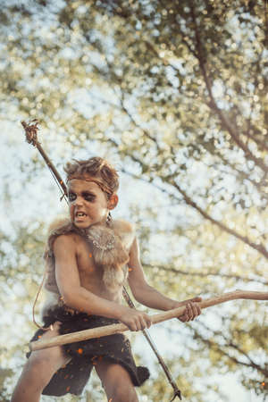 Caveman, manly boy with weapon aggressively shouting. Dramatic action photo of young primitive boy outdoors in forest. Evolution survival concept. Calm boy outside standing in attack pose. Prehistoric tribal man outside on wild nature. Primitive ice age man in animal skin with bow and staff. Creative art fantasy photo. Foto de archivo