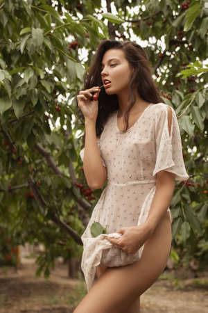 Stunning sexy brunette beauty in garden on nature. Seductive playful girl with sweet cherry, concept of rural harvesting. Gorgeous sensual mixed race Caucasian Asian Woman Eating Cherry. Stockfoto