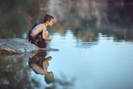 Caveman boy sitting on the rock near river or lake and looking away. Evolution survival concept. Creative art fantasy photo