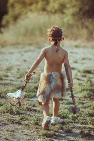 Angry caveman, manly boy with stone axe and animal skull. Prehistoric tribal boy outdoors on nature. Young shaggy and dirty savage, warrior and hunter with weapon. Primitive ice age man in animal skin. Reconstruction of Neanderthal and cro-magnon life