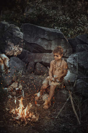 Caveman, manly boy at the fire. Scary young primitive boy outdoors near bonfire. Witch craft concept. Angry caveman, manly boy with horns near bonfire. Prehistoric tribal man outdoors on nature with stone axe. Primitive ice age man in animal skin in forest. Creative art fantasy photo Stok Fotoğraf